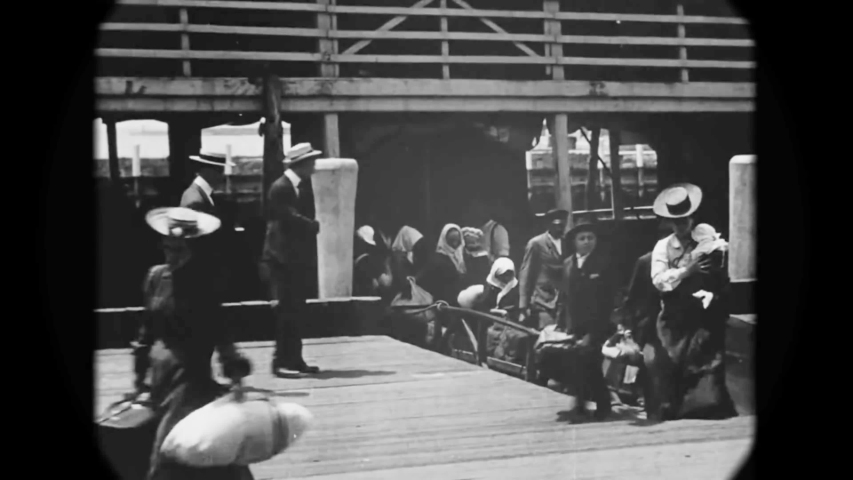 CIRCA 1903 - European immigrants arrive at Ellis Island by ship and disembark on the dock.