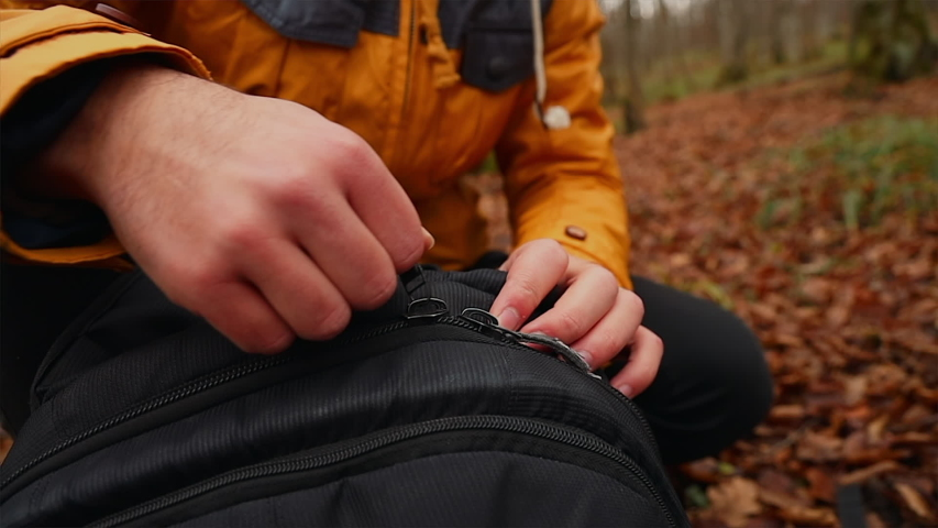 A hiker unzipping his backpack in the forest