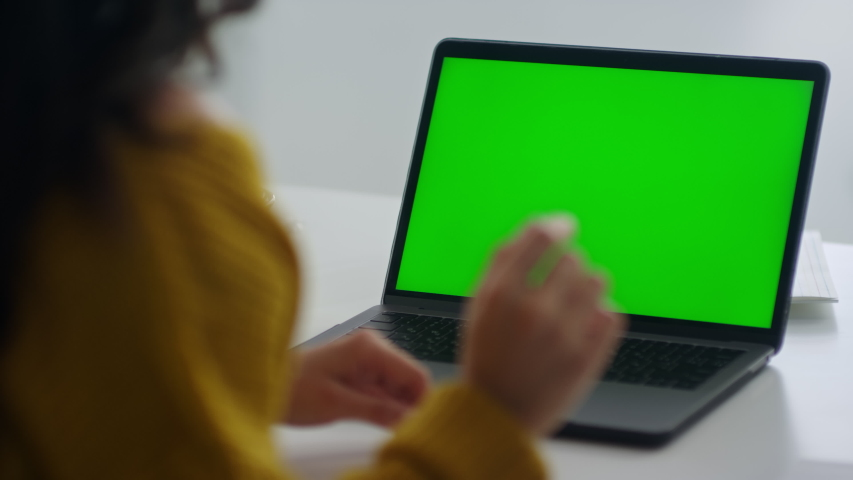 Close up business woman talking on video conference in office. Unrecognized woman looking green screen laptop computer. Side view of girl explaining with gestures in slow motion. Chroma key screen Royalty-Free Stock Footage #1048495165