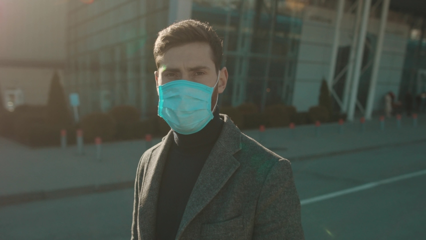 Portrait man wearing Protective Face Mask look at camera COVID-19 coronavirus infection near airport pandemic disease virus male tourist epidemic air health illness slow motion #1048501786