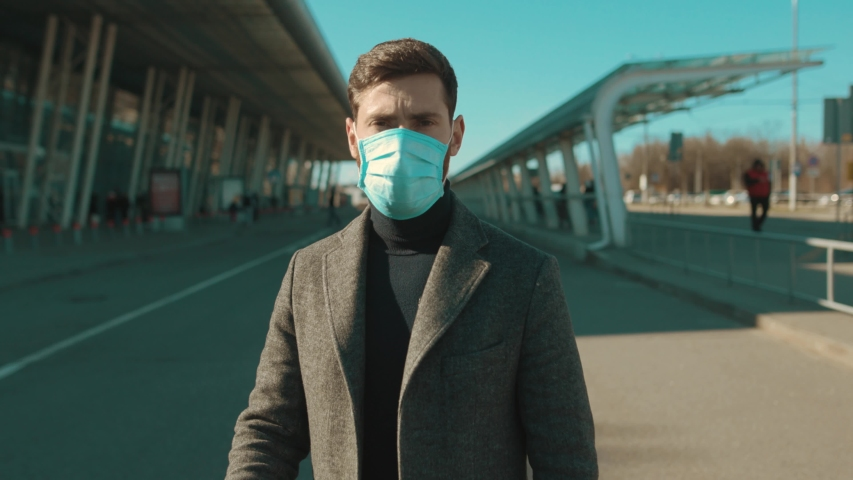 COVID-19 coronavirus infection man wearing Protective Face Mask near airport look at camera serious pandemic disease virus male tourist epidemic air health illness slow motion Royalty-Free Stock Footage #1048501798