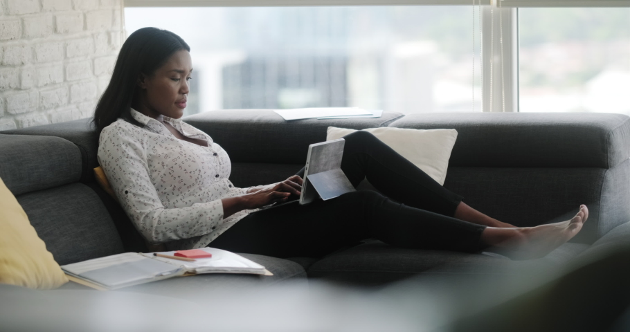 Black woman working from home during quarantine. African american people and mobile work, doing telework. Young businesswoman at work with laptop computer, lying on sofa. Remote work from home office Royalty-Free Stock Footage #1048509655