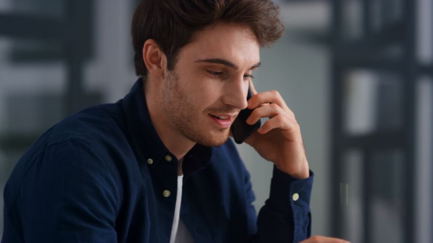Closeup smiling man talking mobile phone in office. Close up of cheerful businessman having phone call at workplace in slow motion. Portrait of happy business man calling phone indoor. Royalty-Free Stock Footage #1048517332