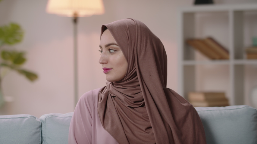 Young beautiful authentic positive arab woman wearing traditional head scarf brightly smiling, successful millenial businesswoman expressing positive emotions on office background 4k footage