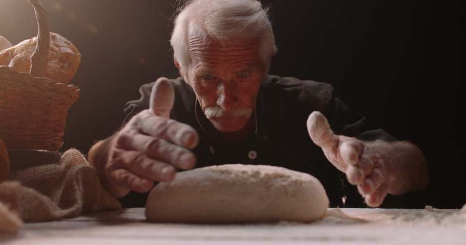 Professional mature caucasian baker putting flour on loaf of bread dough with passion, retired pensioneer enjoying his new hobby, isolated on black background 4k footage