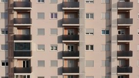 Exterior of a high-rise multi-story apartment building - facade, windows and balconies. Establishing shot aerial footage.