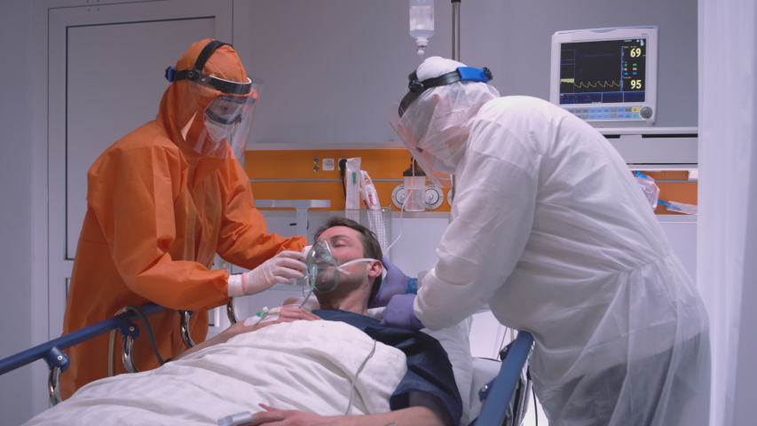 Doctor in Protective Suit Putting on Oxygen Mask on Patient Suffering from Coronavirus - Wide Dolly Shot in Slow Motion | Shutterstock HD Video #1048526950