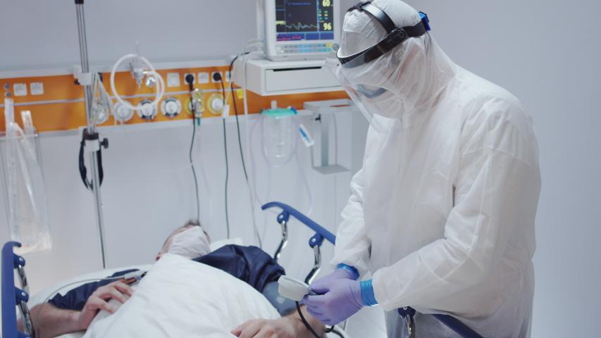 Doctor in Protective Suit Measuring Coronavirus Patient's Blood Pressure - Wide Shot | Shutterstock HD Video #1048527019