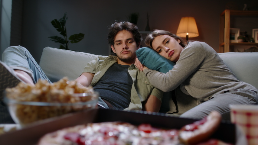 Young caucasian couple extremely frustrated. Bored students are sitting in front of tv, switching channels with remote and eating unhealthy food, tired after hard day 4k footage Royalty-Free Stock Footage #1048527208