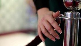 Closeup of women hand opening red velvet rope