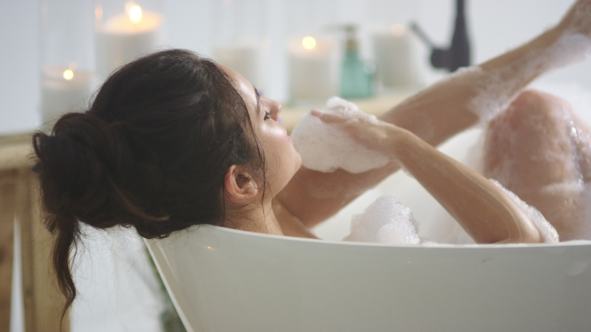 Close up relaxed woman touching skin with foam in bath. Side view of sexy girl taking bathtub at home. Romantic brunette woman relaxing bath in slow motion.