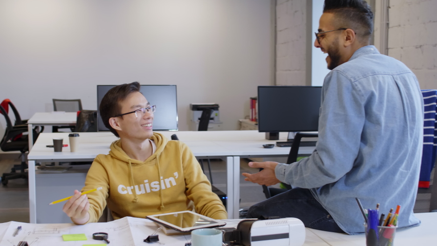 Tracking shot of young multiethnic colleagues working in open space office: using smartphone, discussing project via video call and talking about job and shaking hands | Shutterstock HD Video #1048545757
