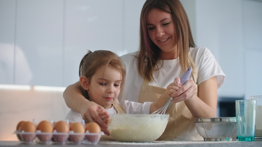 Caucasian mother and daughter having fun while making dough on kitchen. Happy family in the kitchen. Child daughter preparing the dough, bake cookies. | Shutterstock HD Video #1048554562