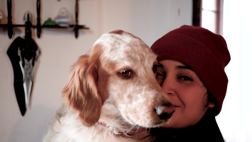 A beautiful Argentinian girl hugging and kissing her dog friend