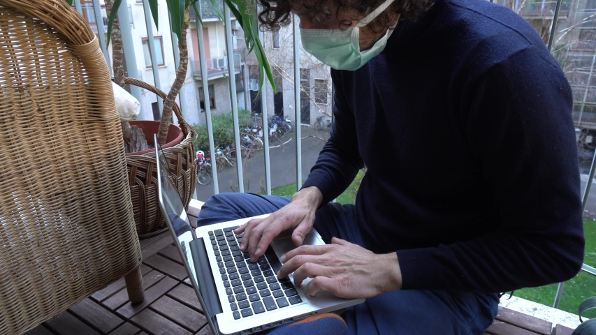 40 years old business man in quarantine working from home with laptop wearing protective mask - Smart working during n-cov19 Coronavirus global epidemic lockdown , conference call on the balcony Royalty-Free Stock Footage #1048571029