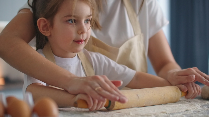 Mother Helping Daughter Roll Dough in Kitchen to Bake Cookies. Mom and daughter bake pizza in the kitchen together. Girl helps her mom to roll out the dough with a rolling pin.  | Shutterstock HD Video #1048572580