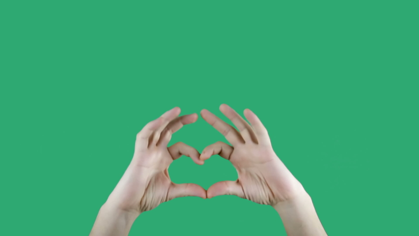 Male hand making heart shape gesture isolated on green screen chromakey background.  | Shutterstock HD Video #1048594816