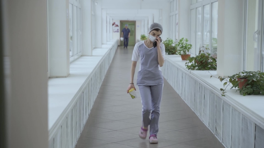 Masked doctor walks down corridor with tests at Russian Moscow hospital at quarantine Royalty-Free Stock Footage #1048598356