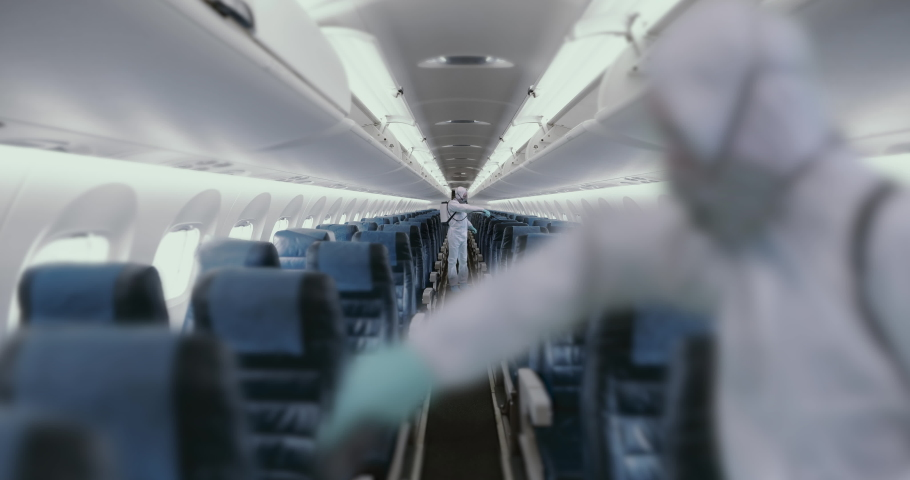 HazMat team in protective suits decontaminating airplane cabin during virus outbreak. Coronavirus, COVID-19 | Shutterstock HD Video #1048599304