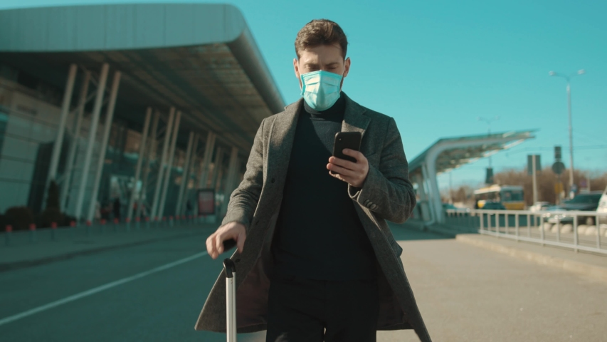 Close up man wearing Protective Face Mask use phone coughs hold suitcase COVID-19 coronavirus infection near airport pandemic disease virus male tourist epidemic air health illness slow motion Royalty-Free Stock Footage #1048605919
