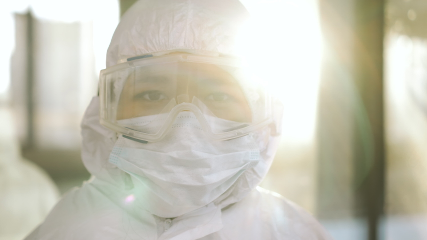 Portrait of epidemiologist protecting patients from coronavirus COVID-19 in mask. Global pandemic epidemic, Europe, Italy, USA. Doctor virologist working in suit, glasses. Appearance from blur