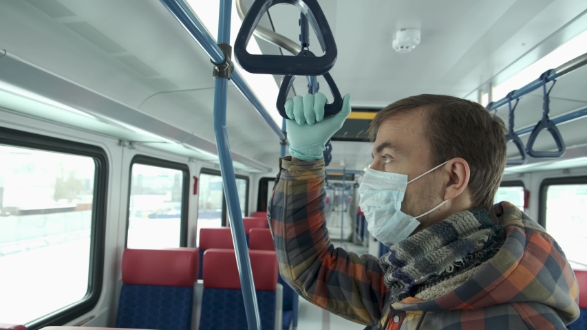 Disease outbreak, stop coronavirus covid-19 pandemic, virus protection, quarantine. Adult man with medical protective mask and gloves inside empty public transport. Protect yourself. Royalty-Free Stock Footage #1048614559