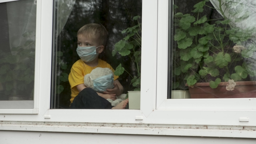 Bored child on home quarantine. Boy with teddy bear both in protective medical masks sits on windowsill and looks out window. Allergy, covid-19 coronavirus pandemic, prevention epidemic.