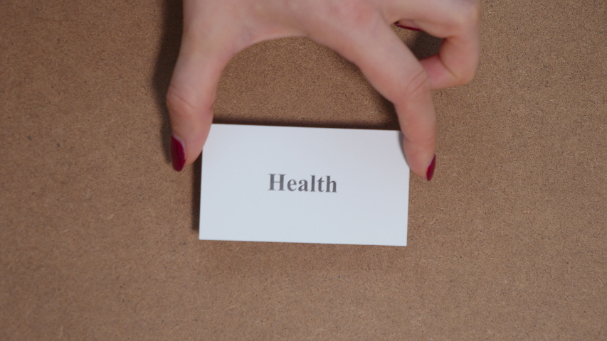 HEALTH. Top shot - Hand puts paper card with printed word - close up . CORE VALUE concept. | Shutterstock HD Video #1048617358