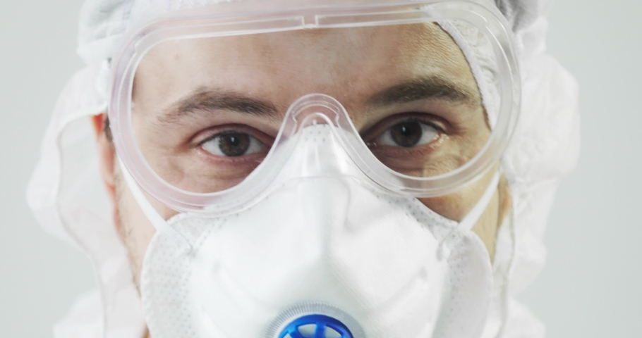 Human man doctor in protective clothes during coronavirus pandemic, portrait. Part of face in suit, mask and glasses on white background in clinic or hospital. Protection from epidemic concept. | Shutterstock HD Video #1048617946