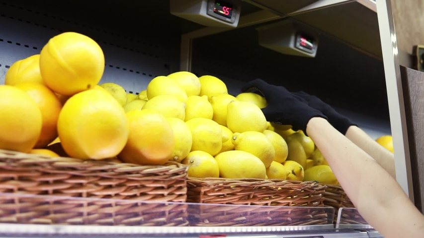 Close up of female worker in black gloves stocking the lemons in supermarket. Young employee at work. Curly female arranging lemons on shelf. Slow motion | Shutterstock HD Video #1048620466