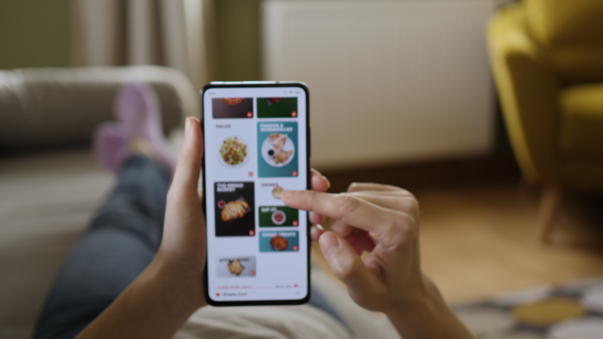 Orders Pizza Using Online Delivery. Woman Orders Food Home In Online Store Using a Smartphone. Female Ordering pizza using food delivery app. Screen is blurred. Focus on hand. Royalty-Free Stock Footage #1048634653
