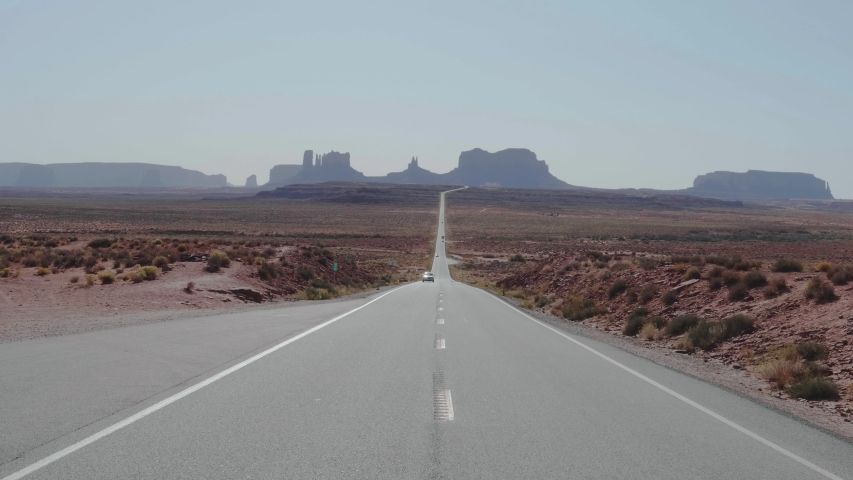 Travelers and tourists driving by cars along famous straight road leading to Butte and Mesa mountains in monument valley, Utah, USA. Panorama from bottom to up of the remains of red rock formations