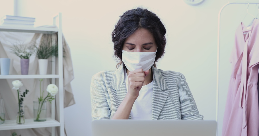 Sick young businesswoman fashion designer wears face mask using computer coughing at home office. Ill female worker working distantly self-isolating having coronavirus flu infection symptom concept.   Shutterstock HD Video #1048637278