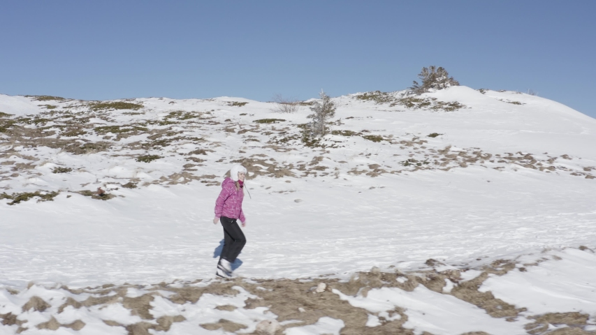 Happy woman walking in snow outdoor nature in mountains covered with snow. Alone hiking in sunny morning in winter. Beautiful caucasian young model smiling and enjoying cold weather - 4k