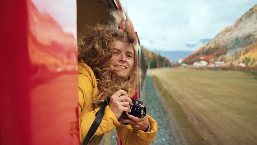 Follow split shot of woman walk to and hang out of train carriage window. Cinematic and inspiring travel blogger live motivational adventure. Happy young woman on train vacation
