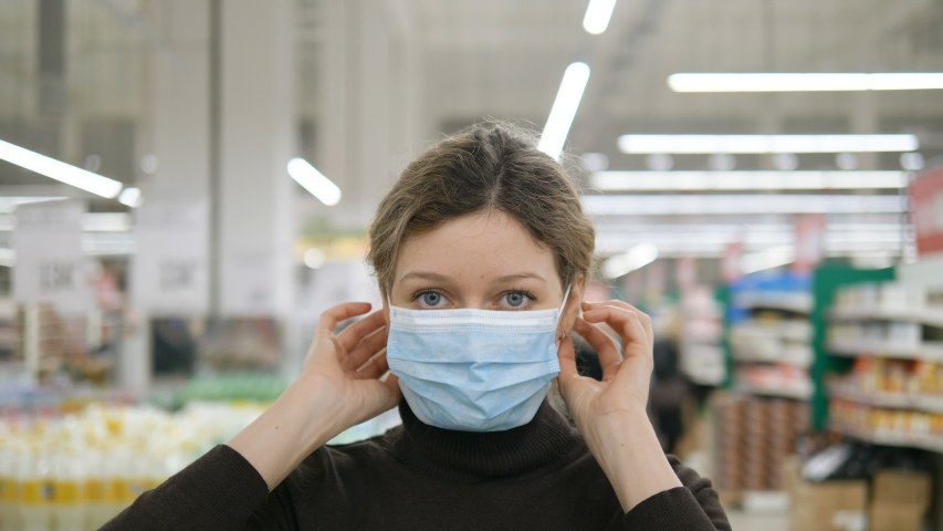 A young woman puts on a medical mask in a grocery supermarket close-up and looks at the camera, protection from coronavirus, shopping in a store to wait out the quarantine.