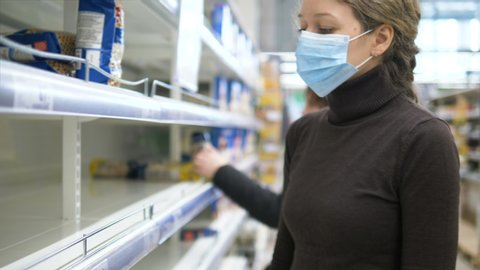 A woman in a medical mask takes the last bag of food in the supermarket. Empty store shelves due to pandemic panic