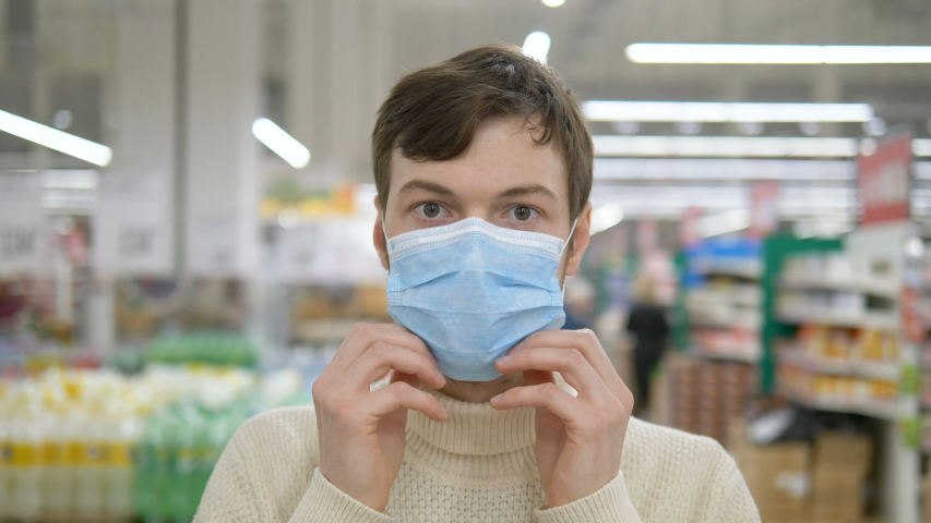 A young man puts on a medical mask to protect against the epidemic, a close-up portrait. Protection from the coronavirus pandemic. Royalty-Free Stock Footage #1048641751