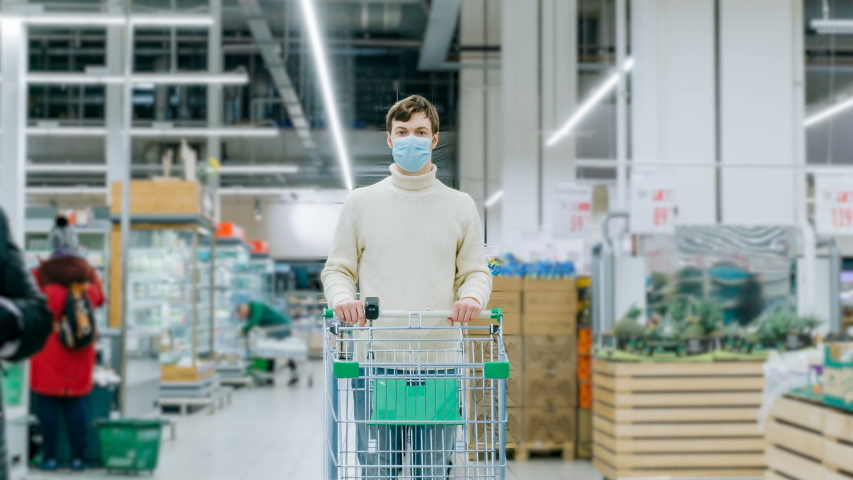 A man in a medical mask stands in a supermarket with a timelapse grocery cart. Protection from the coronavirus epidemic, purchase of products for quarantine. Royalty-Free Stock Footage #1048641757