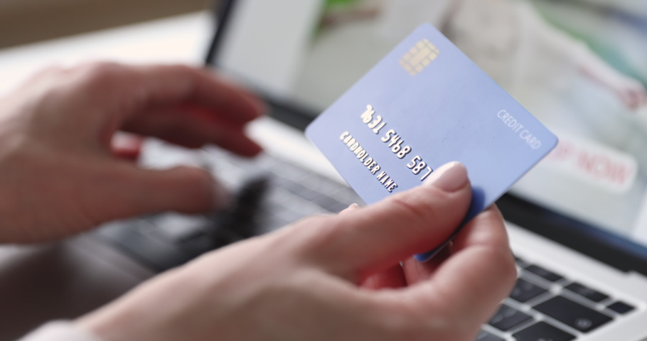 Female hands of cardholder holding credit card making e bank online payment. Woman consumer paying for purchase in web store using laptop technology. Ecommerce website payments concept. Close up view | Shutterstock HD Video #1048645585