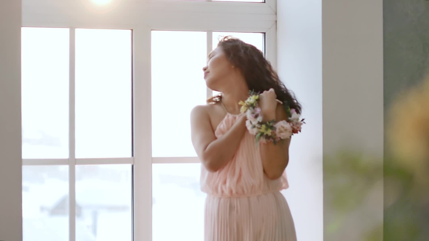 Portrait of a stunningly beautiful Asian young woman in a delicate pink dress with spring flowers in her hands. Woman enjoying flowers in a bright room under the morning sun. Slow motion | Shutterstock HD Video #1048663999