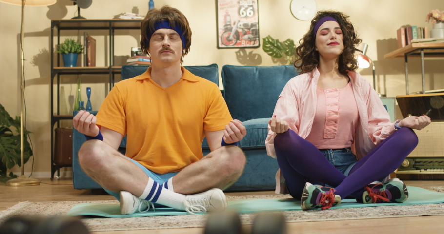 Funny retro style couple of Caucasian man and woman meditating on yoga mat indoors. Pretty smiling happy young girl fooling around with man while practicing meditation at home. Sport concept | Shutterstock HD Video #1048678912