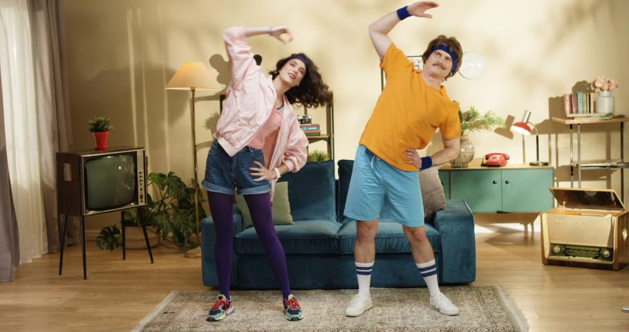 Cheerful Caucasian male and female retro style models stretching muscles while standing in room. Funny couple of man and woman exercising at home near sofa. Indoor pair workout at home. 50s concept | Shutterstock HD Video #1048678936
