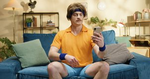 Retro style Caucasian funny sportsman video chatting on smartphone and showing up his muscles while sitting on blue sofa at home. American style athlete of 50s showing biceps to phone camera indoors