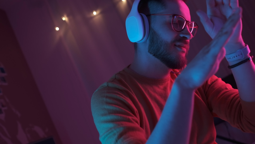 Handsome man listening music using headphones and mobile phone in living room in colourful neon light. Student resting after work and enjoying music. Dance smooth hand movements to the rhythm