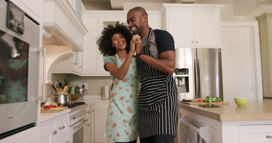 Side view of a mixed race couple enjoying their time together in an apartment, standing in a kitchen, wearing cooking aprons, cooking, dancing, in slow motion. Social distancing and self isolation