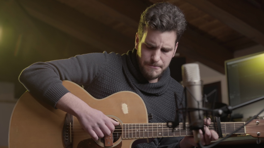 Still shot of Young creative male guitarist singer in real home recording studio, recording sitting in front of condenser microphone, modern, professional audio workspace, audio wave form on computer  Royalty-Free Stock Footage #1048682986