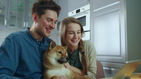 Happy Young Couple Petting Their Dog While Making Video Call at Home Waving Hello to Friends, Family, Smiling, Laughing, Talking. Online Communication Concept. Slow Motion Cinematic Shot