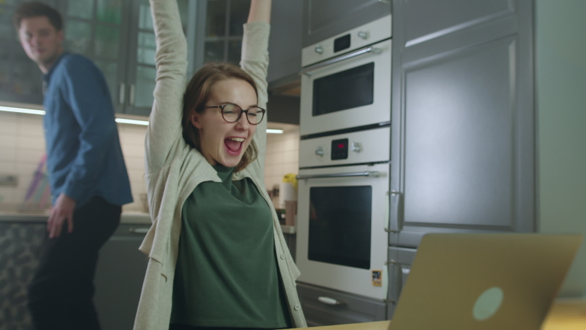 Slow Motion Shot of Young Woman Using Laptop While Sitting in Kitchen with Man in Background. She Learns Good News Making Her Very Happy and He Approaches Her to Congratulate and Hug | Shutterstock HD Video #1048684702