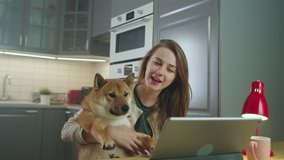 Side View of Young Woman Sitting at Table and Petting Her Dog While Making Video Call. Attractive Girl Video Chatting, Smiling, Laughing, Talking. Online Communication Concept. Slow Motion Shot